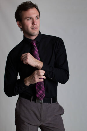 young  cuffs: Young man in a suit  Studio shot over grey