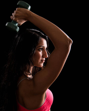 woman lifting weights: Young woman performing triceps extension exercise. Studio shot over black.