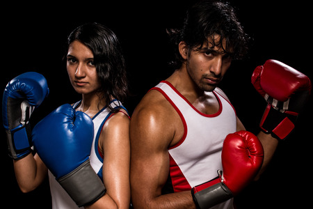 sexes: Male and female boxers Battle of the sexes. Studio shot over black.