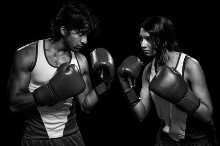 Male and female boxers  Battle of the sexes   Studio shot over black Stock Photo - 27841373
