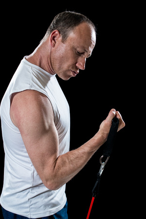 bicep: Bicep curl exercise with resistance band. Studio shot over black.