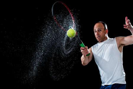 Tennis action shot. Forehand. Studio shot over black. 写真素材