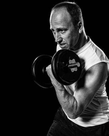 fitness hombres: Bíceps ejercicio rizo con mancuernas. Tiro del estudio sobre negro.