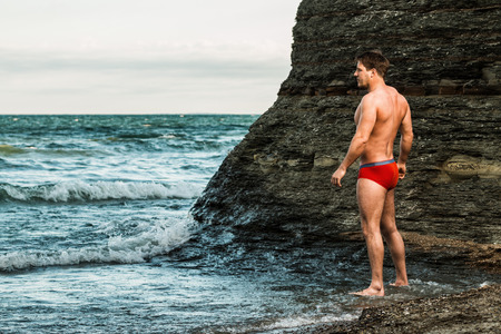 lake beach: Muscular man on a beach in underwear. Stock Photo