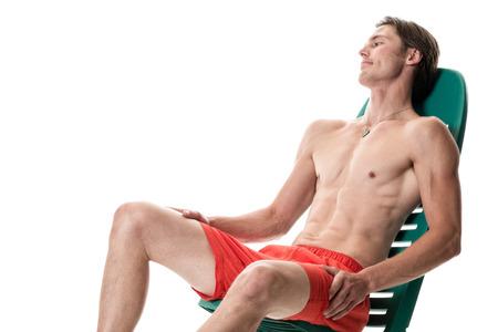 hombre sentado: Hombre en traje de baño. Estudio de disparo sobre el blanco. Foto de archivo