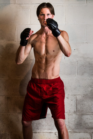 adult wall: Young adult martial artist in front of a concrete block wall. Stock Photo