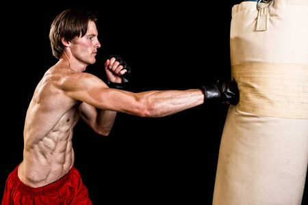 martial artist: Young adult martial artist with heavy bag. Studio shot over black. Stock Photo