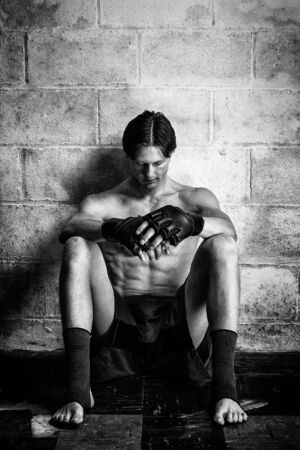 martial artist: Young adult martial artist in front of a concrete block wall. Black and white. Stock Photo