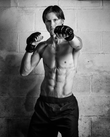 adult wall: Young adult martial artist in front of a concrete block wall. Black and white. Stock Photo