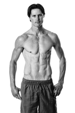 Man in swimwear. Studio shot over white. Black and white.