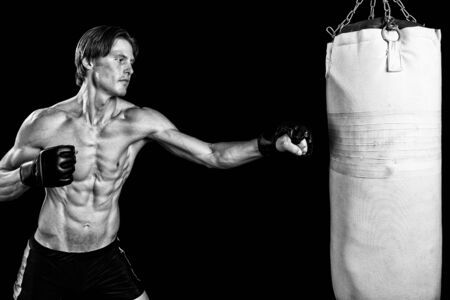 martial artist: Young adult martial artist with heavy bag. Studio shot over black. Black and white.