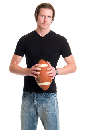 tee shirt: Man in jeans and black tee shirt with football. Studio shot over white.
