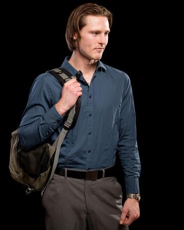 slacks: Man with backpack.  Studio shot over black. Stock Photo