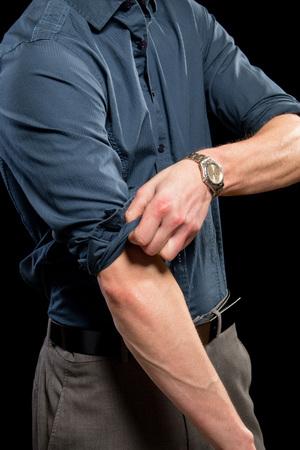 sleeve: Adult man rolling up his sleeves. Studio shot over black.