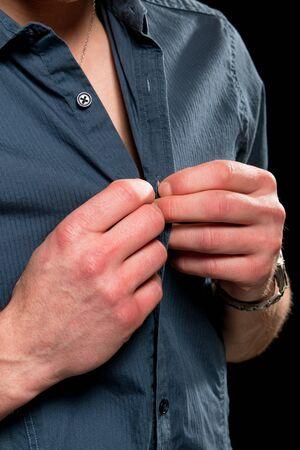unbutton: Adult man buttoning or unbuttoning his shirt. Studio shot over black.