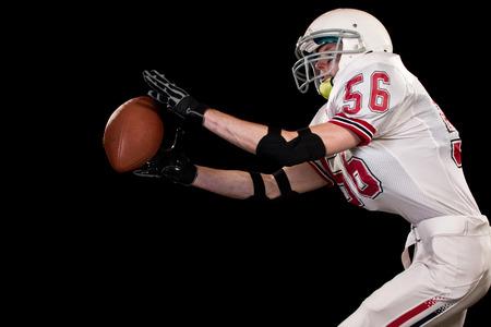 catches: American football player. Studio shot over black. Stock Photo