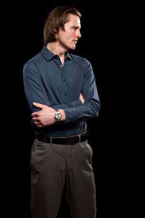 man shirt: Man in blue shirt and grey slacks. Studio shot over black.