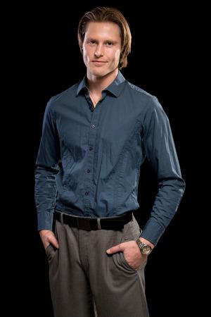 slacks: Man in blue shirt and grey slacks. Studio shot over black.