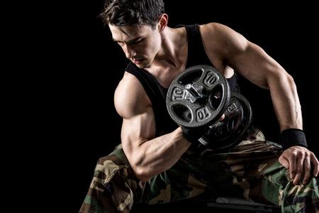 male athlete: Concentration curl exercise. Studio shot over black.