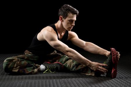 male athlete: Athletic man stretching. Studio shot over black.