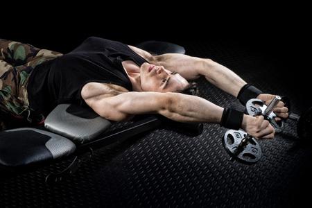 pull over: Dumbbell pull over exercise. Studio shot over black. Stock Photo