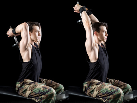 military press: Overhead triceps press exercise. Studio shot over black. Stock Photo