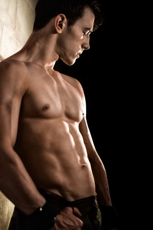 posing: Athletic man posing with flexed muscles against wall. Stock Photo