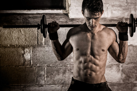 fits in: Athletic man exercising with a barbell. Stock Photo