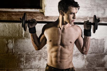 fitness hombres: Atlético hombre haciendo ejercicio con una mancuerna. Foto de archivo