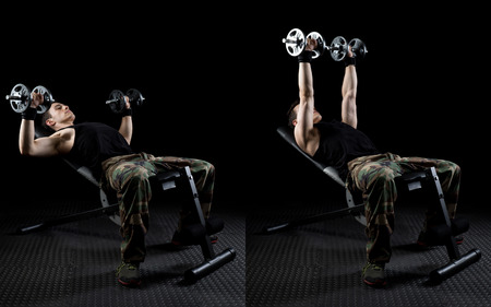 military press: Inclined dumbbell chest press exercise. Studio shot over black.