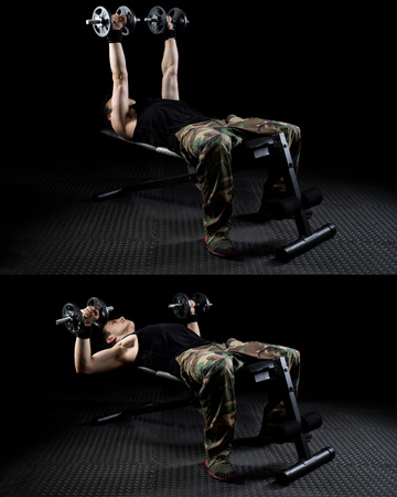 Dumbbell chest press exercise. Studio shot over black. Reklamní fotografie