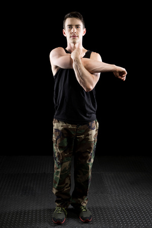 fits in: Athletic man stretching. Studio shot over black.