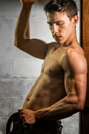 Athletic man posing with flexed muscles in doorway. Stock Photo