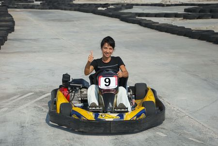 prety brunette driving a kart on karting circuit Stock Photo