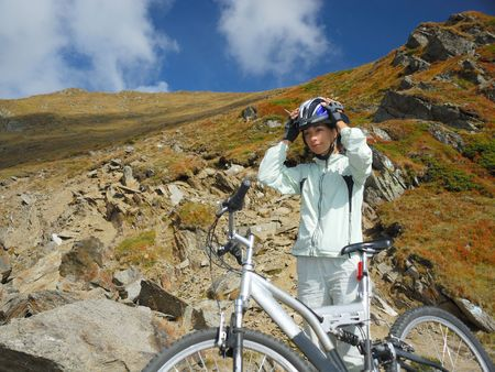 fastens: young women fastens her helmet for mountain bike trail  Stock Photo