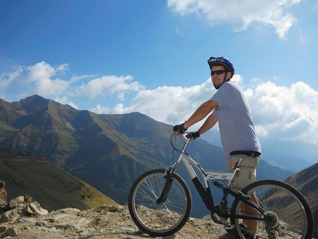 young man with a full suspension bike in mountains enviroment photo