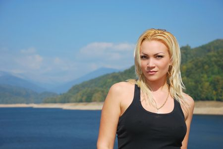 portrait of a beautiful young blonde with mountains and lake as background Stock Photo