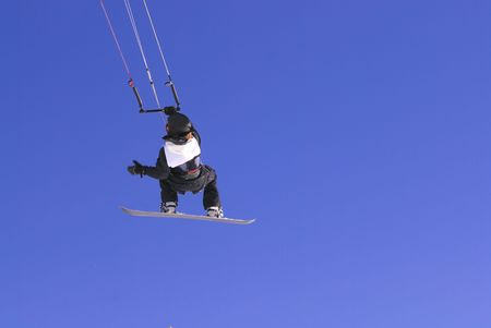 kiter: kiter with snowboard flying on the clear blue sky Stock Photo