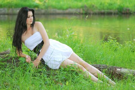 beautiful young lady resting on log and grass Stock Photo