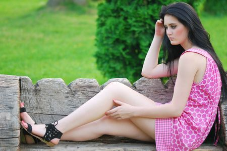 beautiful young lady relaxing on a bench in park Stock Photo
