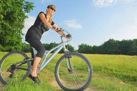 smiling pretty girl riding a bike in green environment Stock Photo