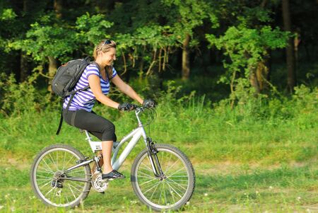 happy blonde young woman traveling on country side with bike