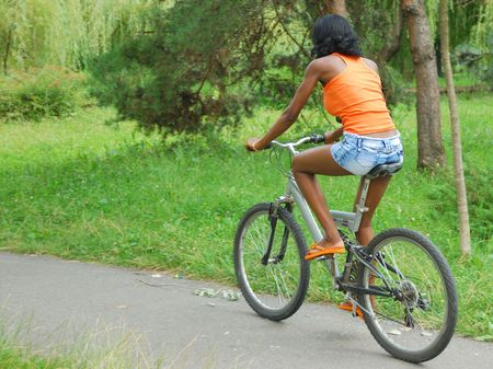 african girl having fun riding a bike in park Stock Photo - 7421635
