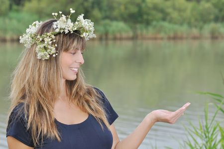 Beautiful young lady with flowers crown looking at open hand Stock Photo