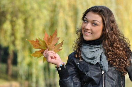 happy young woman showing beautiful maple leaves