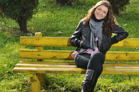 jacket: Beautiful teenager with lovely smile sitting on bench in park