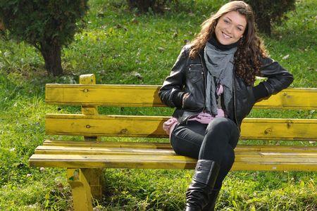 chaqueta de cuero: Bella adolescente con sonrisa encantadora, sentado en el banquillo en el Parque