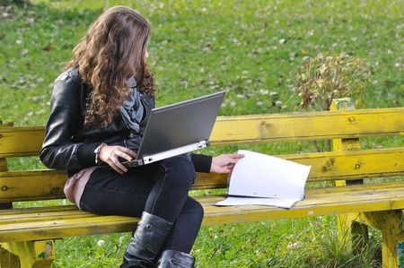 woman studying with a laptop and papers on bench in park photo