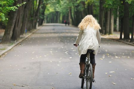 back view of an woman riding a bike in park in autumn