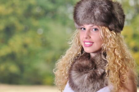 blonde curly hair: beautiful Caucasian girl wearing fur cap and collar with green copy space Stock Photo